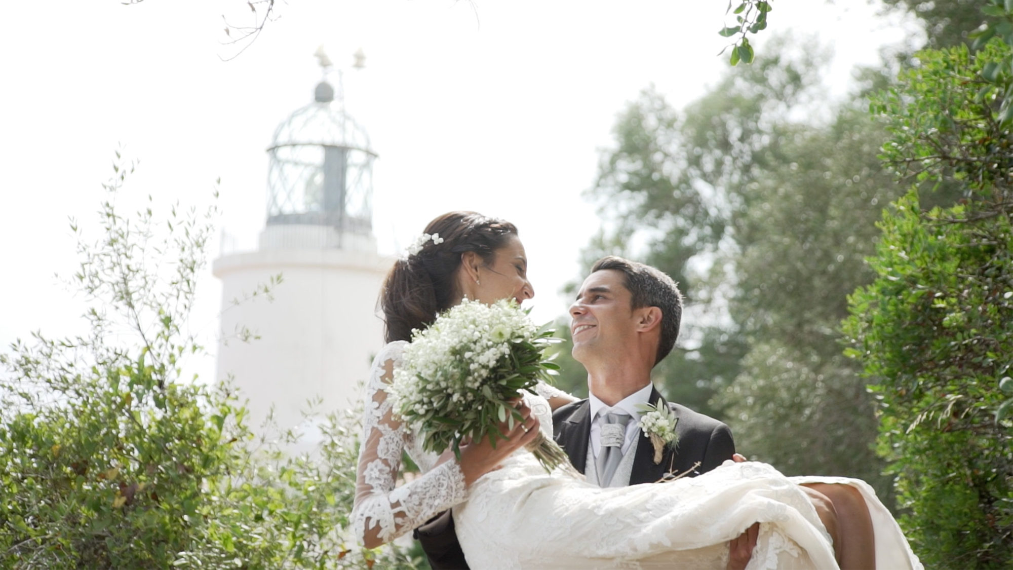 Miradas de amor entre recién casados con faro de fondo. Love lookings between newly wed couple by a lighthouse.