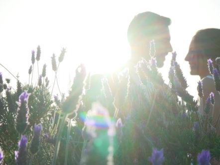 Pareja felic detrás de flores